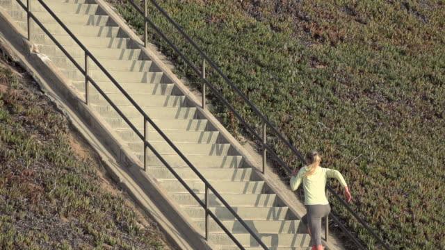 stockvideo's en b-roll-footage met a woman running stairs. - haar naar achteren