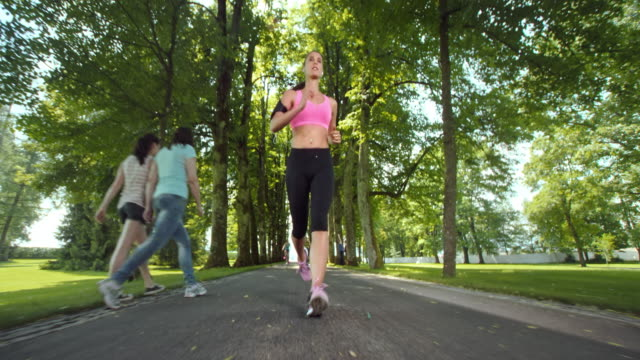 SLO MO TS Woman running through a beautiful sunny avenue