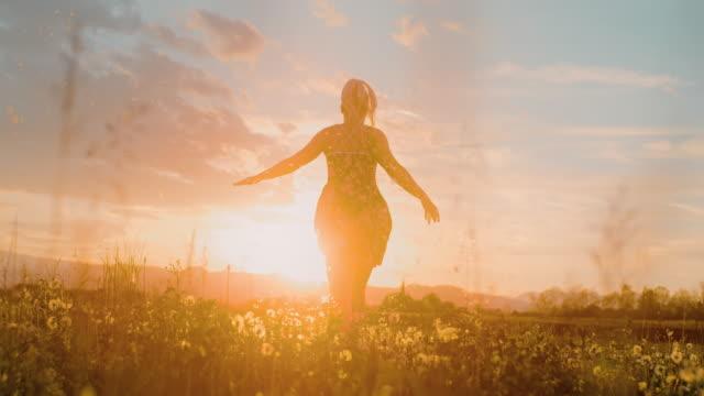 タンポポの分野を走るslo mo女性 - 裸足点の映像素材/bロール