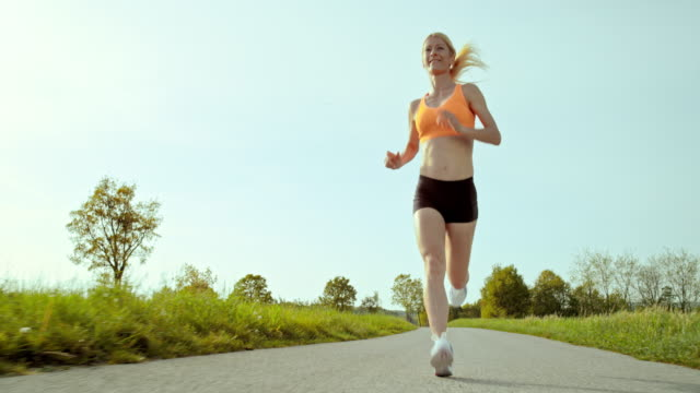 SLO MO TS Woman running through countryside
