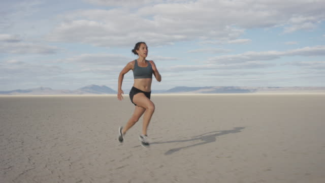 woman running through expansive dessert - endurance stock videos & royalty-free footage