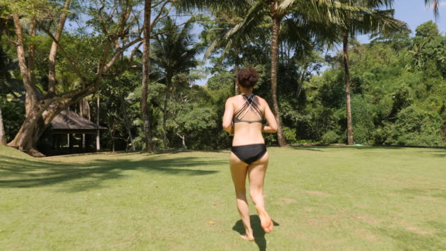 woman running through grass lawn in swimsuit - tracking shot stock videos & royalty-free footage