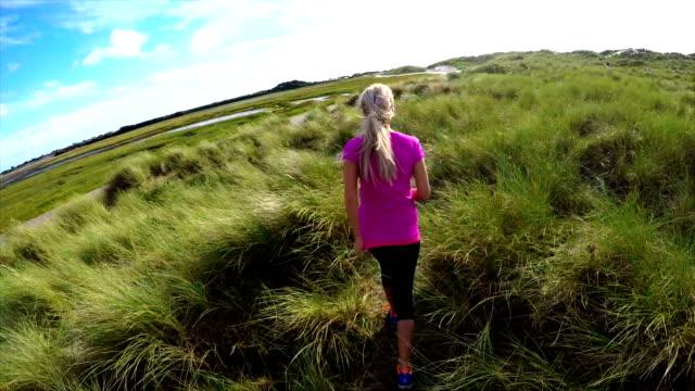 vídeos y material grabado en eventos de stock de woman running through grass - rosa brillante