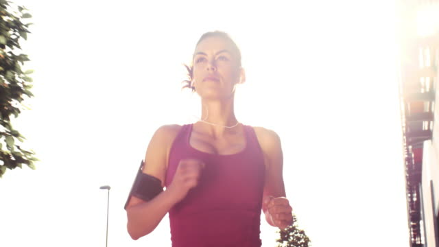 slo mo ts woman running through the city on a hot day - back lit woman stock videos & royalty-free footage