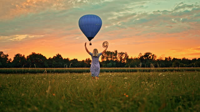 super slow motion woman running through the meadow and waving towards the flying hot air balloon - 1 minute or greater stock videos & royalty-free footage