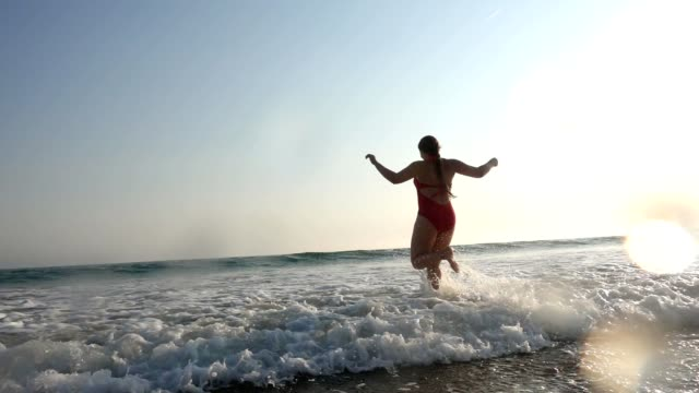Woman running through water at beach
