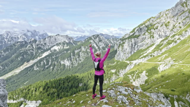 aerial woman running to the mountain ridge and raising her hands in the air above the sunny valley - mountain peak stock videos and b-roll footage