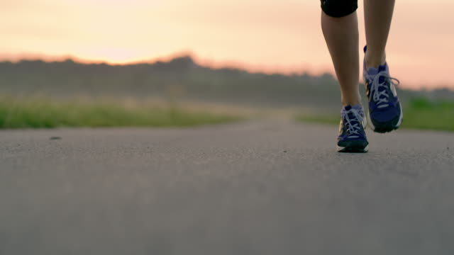 slo mo woman running toward the camera - muoversi in una direzione video stock e b–roll
