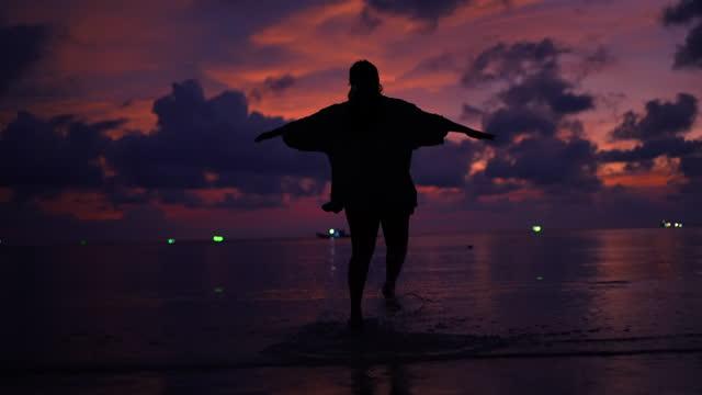 woman running toward the sea on beach at sunset - human limb stock videos & royalty-free footage
