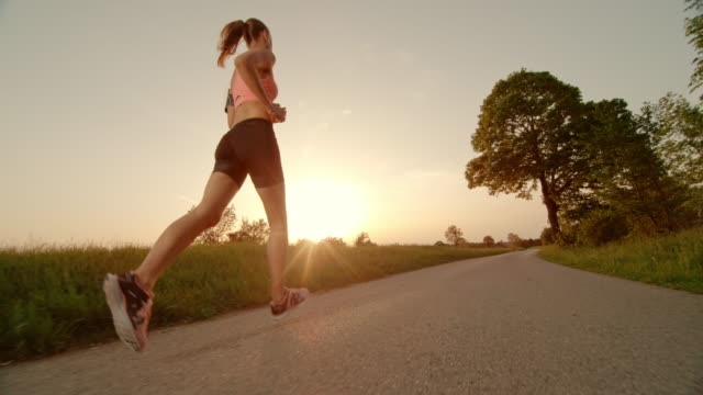 slo mo ts woman running towards setting sun - activity stock videos & royalty-free footage