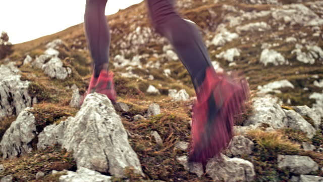 Mujer que corre por un prado rocoso de las montañas