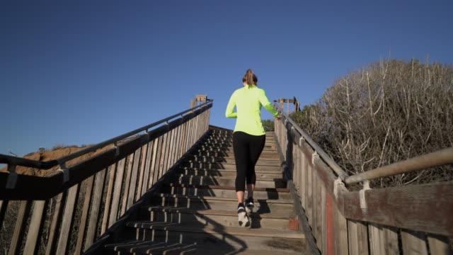 ws ts rv woman running up stairs - steps and staircases stock videos & royalty-free footage
