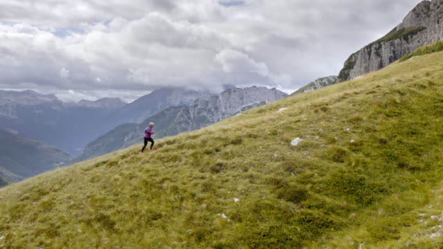 AERIAL Woman running up the mountain with beautiful view of the surrounding nature