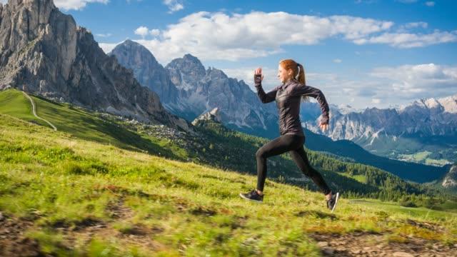 vidéos et rushes de femme exécutant la montée sur une prairie herbeuse avec des montagnes en arrière-plan - joggeuse