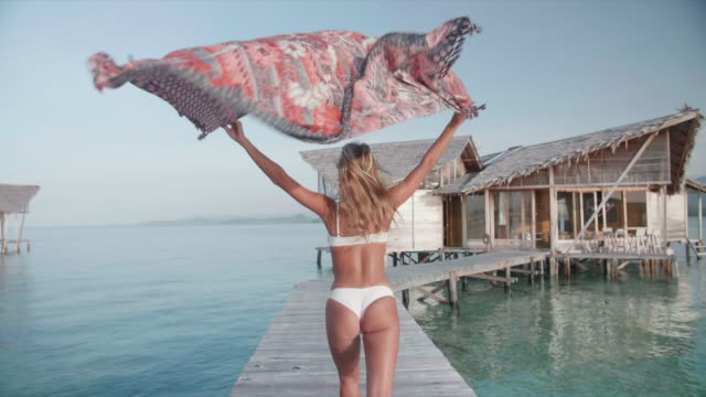 a woman running with a sarong on a deck over water at sunset, traveling at an exotic hotel resort. - sarong stock-videos und b-roll-filmmaterial
