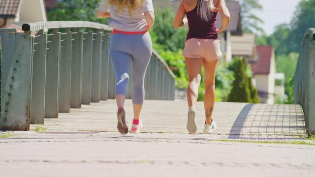 市内の橋を渡って女性のパーソナルトレーナーと一緒に走っている女性 - sunny点の映像素材/bロール
