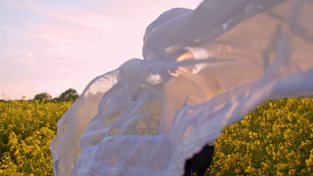 SLO MO Woman running with her shawl in a canola field