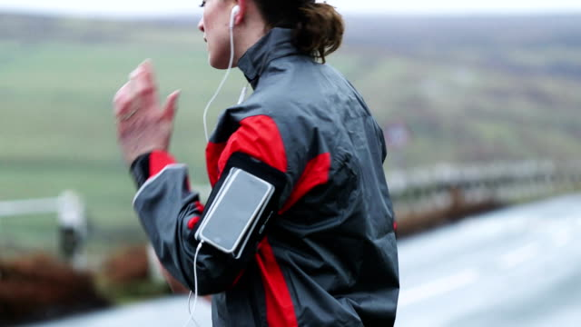 woman running with smart phone - one mid adult woman only stock videos & royalty-free footage