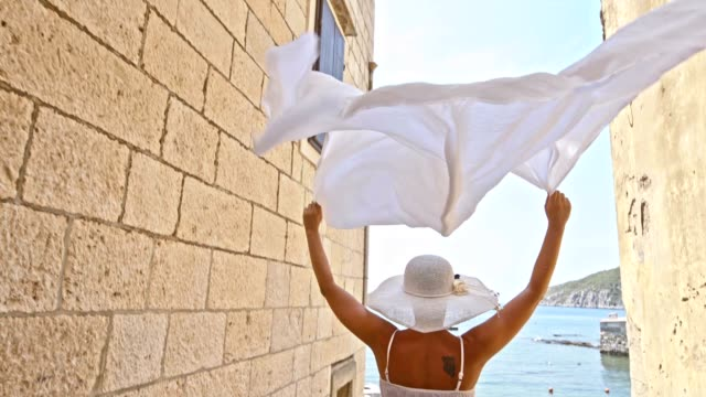 SLO MO Woman running with white shawl to the beach