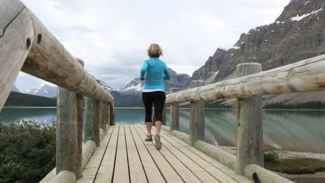 vídeos y material grabado en eventos de stock de woman runs across wooden bridge at mountain lake - corredora de footing