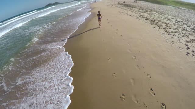 woman runs along edge of sea surf, wearing bikini - brasile meridionale video stock e b–roll