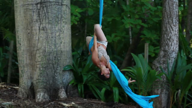 ms ts woman runs and jumps up into fabric hanging from large tropical trees and performs aerial circus dance / montezuma, puntarenas, costa rica - kelly mason videos stock videos & royalty-free footage