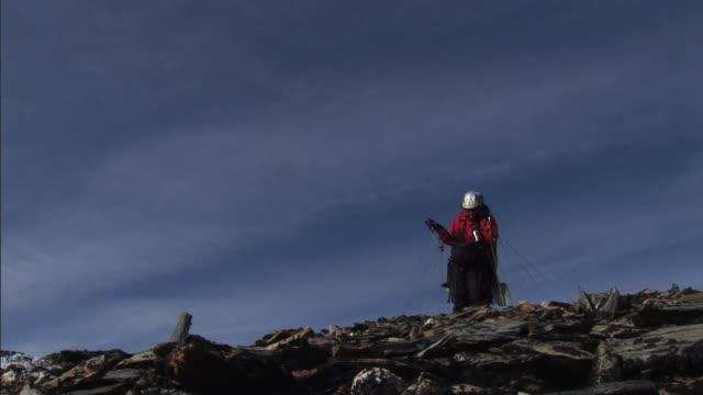 vidéos et rushes de a woman runs at the edge of a cliff with a parachute. - parapente