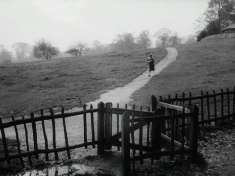a woman runs down a muddy path to place a cancelled sign on a poster advertising a garden fete 1953 - poster stock videos & royalty-free footage