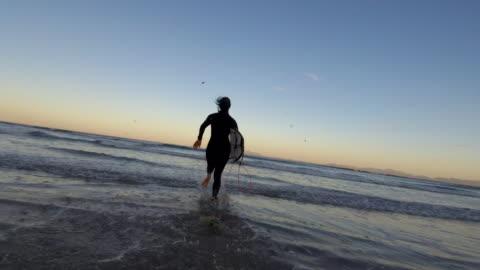vídeos y material grabado en eventos de stock de mujer se corre en las olas con su tabla de surf - surf