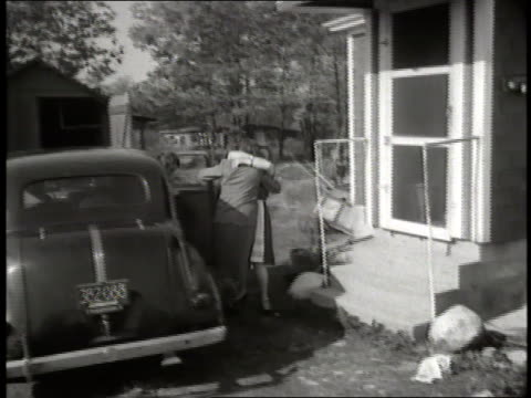 woman runs out of her house and excitedly greets jewish refugees as they get out of a car. - anno 1952 video stock e b–roll