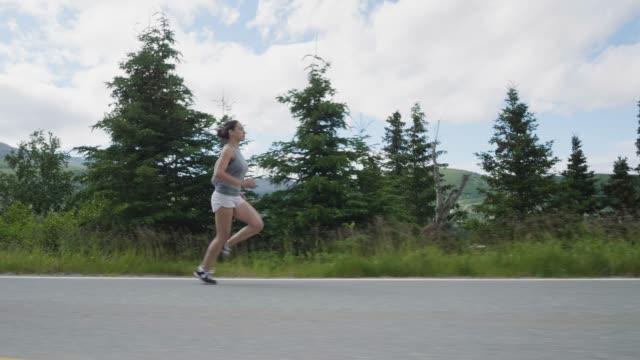 vidéos et rushes de femme solo de courses le long de la route - joggeuse