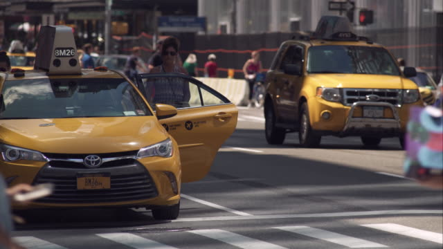 woman runs to catch up with friend getting into taxi on busy new york city street - yellow taxi点の映像素材/bロール