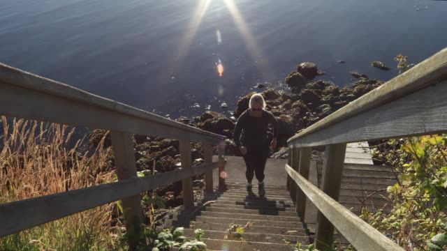 woman runs up wooden steps above sea, sunrise - steps and staircases stock videos & royalty-free footage