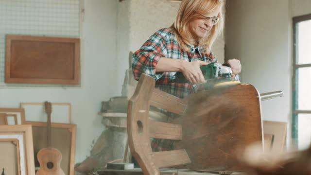 vídeos y material grabado en eventos de stock de mujer lijar silla con máquina de arena - herramienta de mano