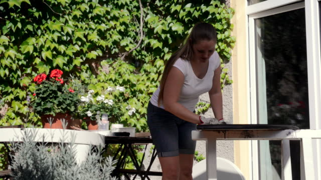Woman sanding old table outdoor.