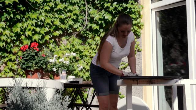 vidéos et rushes de woman sanding old table outdoor. - genderblend