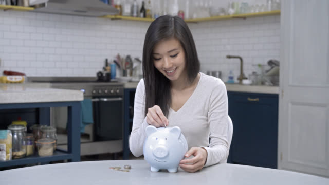 Woman saving coins putting them in her piggy bank