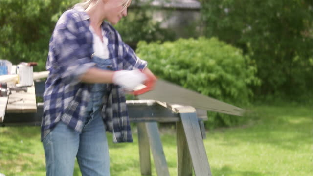 a woman sawing in a garden sweden. - dungarees stock videos and b-roll footage
