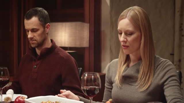 Woman saying grace before Thanksgiving meal with family at table