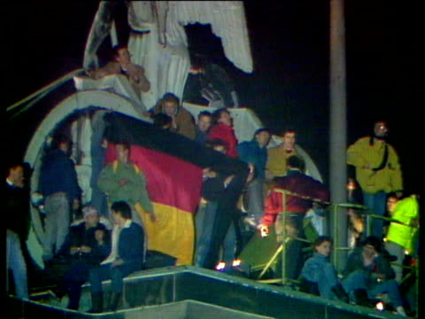 stockvideo's en b-roll-footage met woman scaling pipe along berlin wall; people celebrating new year's on top of brandenburg monument; crowds of people on top of berlin wall; people... - berlijnse muur