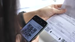 Woman Scan QR Code for Bill Payment with mobile phone