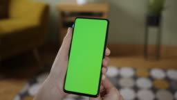 Woman Scanning Fingerprint on smartphone with Green Mock-up Screen, Doing Swiping, Scrolling Gestures. Female Mobile Phone, Internet Social. Scan Fingerprint Biometric Identity Approval. Security