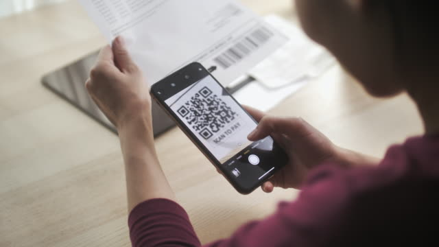 woman scans the qr code on financial bill for online payment at home - human body part stock videos & royalty-free footage