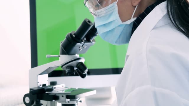 Woman scientist start working with microscope. Microbiologist looking microscope. Microbiology laboratory research.and green screen background.