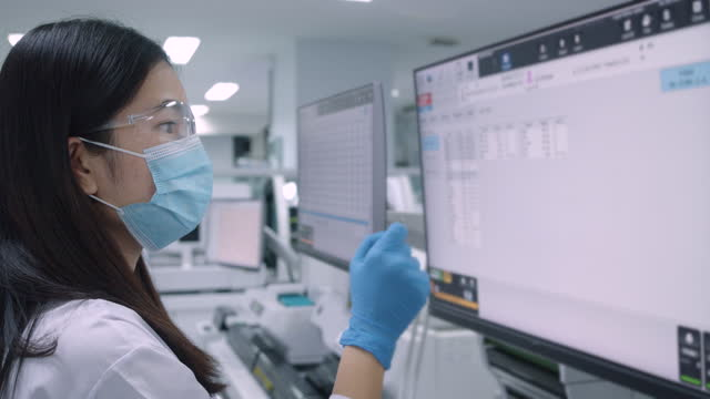 woman scientist touching the touch screen. a blood test with computer equipment. - microbiology stock videos & royalty-free footage
