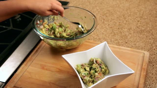 vídeos y material grabado en eventos de stock de pov woman scooping guacamole into a bowl - aguacate