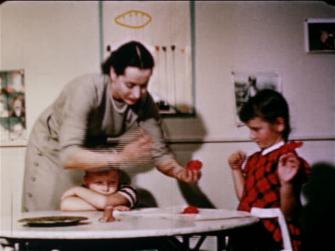 vídeos y material grabado en eventos de stock de 1950 woman scooping out red paint for boy + girl to finger paint on table / educational - maestra
