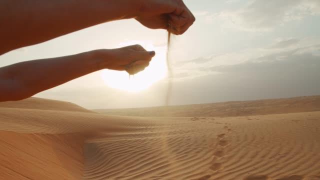 MS vrouw schept zand in de woestijn