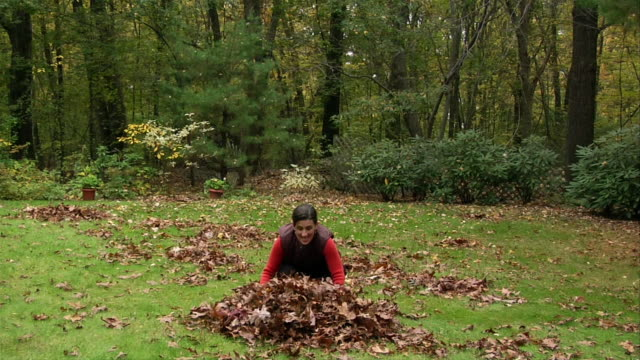 Woman scooping up autumn leaves in backyard / smiling and holding arms out as leaves rain down over her
