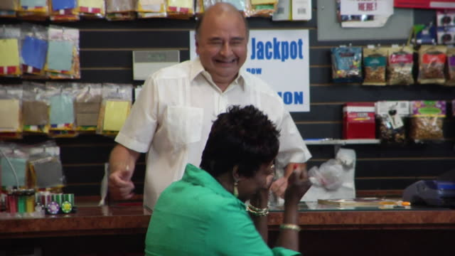 MS Woman scratching scratch-off ticket and winning at convenience store counter/ woman and clerk dancing in celebration/ Brooklyn, New York